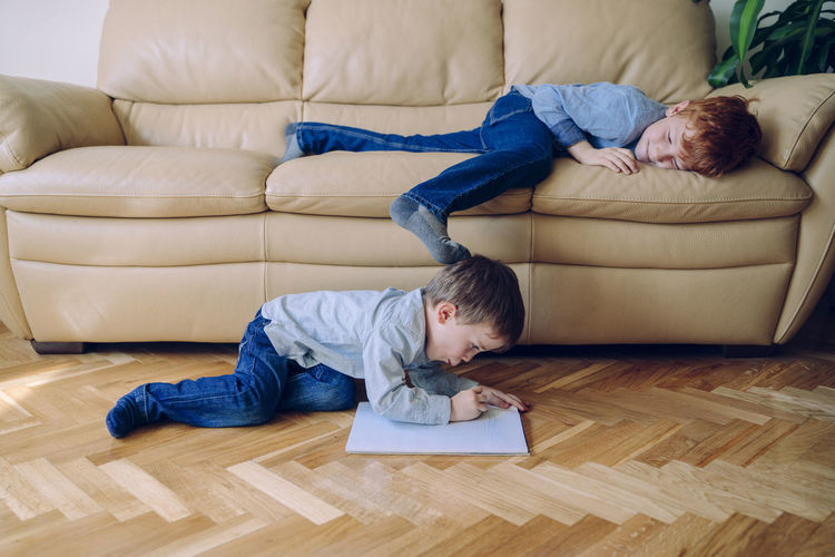 Rear view of boys relaxing on sofa at home
