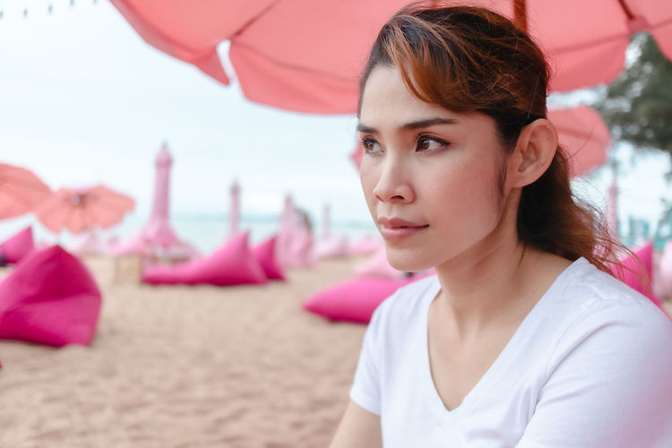 Portrait of young woman looking away at beach