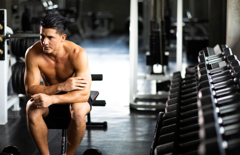 Shirtless man looking away while sitting in gym