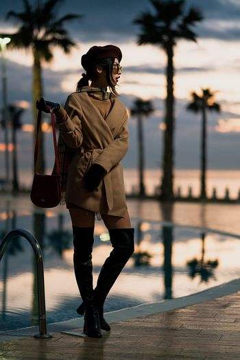 Full Length Of Young Woman Standing At Poolside Against Sky During Sunset