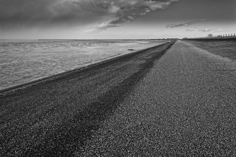 Tire tracks on beach against sky
