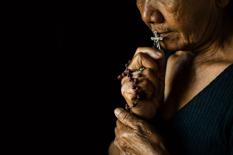 Close-up of senior woman holding rosary while praying against black background