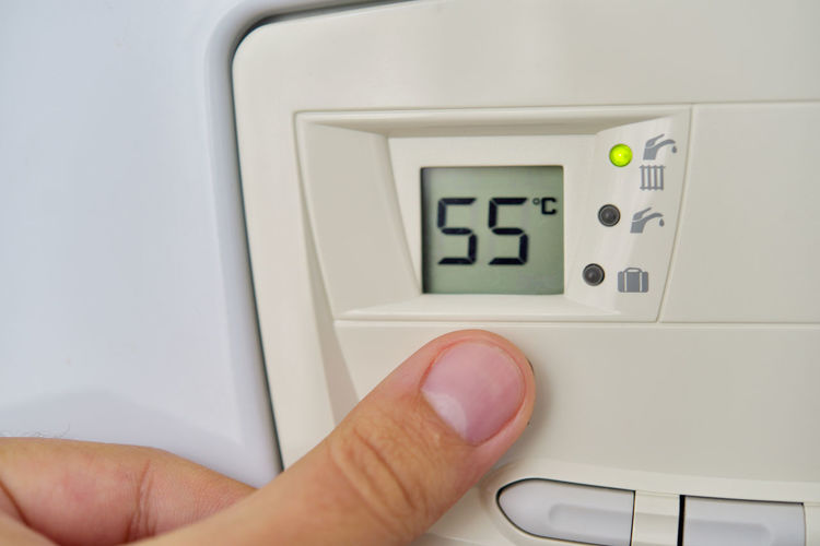 Cropped hand of person touching thermostat