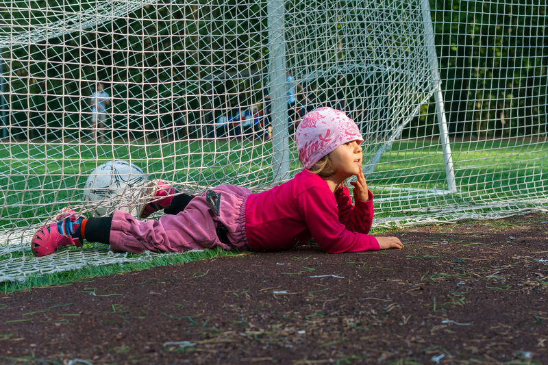 Girl lying on net over field