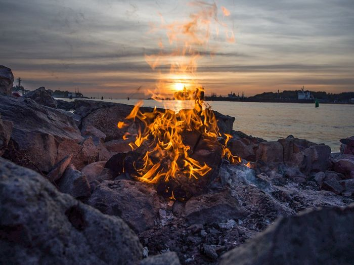 Close-up of campfire on rocks at lakeshore against cloudy sky during sunset