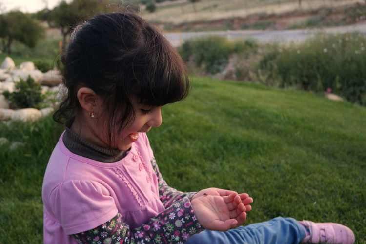 Curious Girl Looking At Insect While Sitting On Grassy Hill