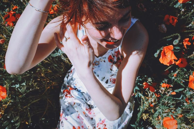 High Angle View Of Cheerful Woman Lying Amidst Orange Poppy Field