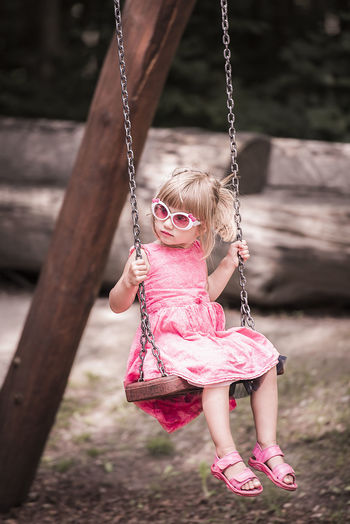 View Of Girl Playing On Swing At Park