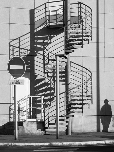 A Shadowy Character Black & White Forbidden Architecture Black And White Building Building Exterior Built Structure City Communication Day Lifestyles Light And Shadow Men One Person Outdoors Railing Real People Shadow Shadowy Character Sign Spiral Staircase Steps And Staircases Text Wall - Building Feature