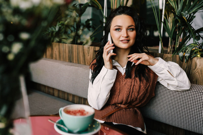 A happy cheerful girl with makeup and hairstyle chatting talks using the phone in a cafe