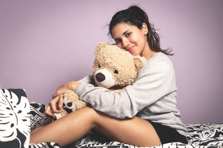 Young beauty latin woman with a teddy bear on her bed. Hug Latin Young Beautiful Woman Beauty Bed Bedroom Candid Cute Happiness Indoors  Latina Legs Love Sitting Teddy Bear Toy Young Adult Young Women