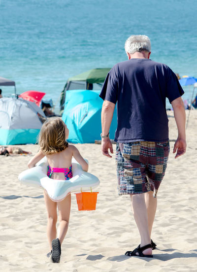 Rear view of father and son walking on beach