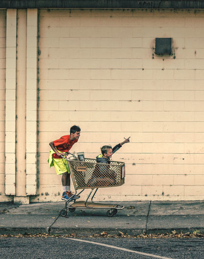 Brothers Playing On Shopping Cart Against Wall