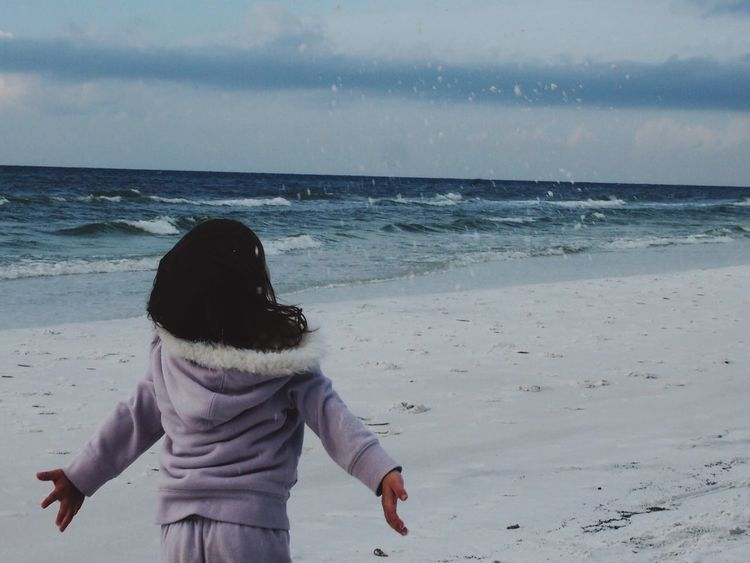 Always Be Cozy Warm Clothing Happy Simple Joys Child Soft Clothes Cold Days Child Playing Beach Water Throwing Sand  Reckless Abandon Joy Joy Of Life Playing With Nature Audience Of One Experimenting... Lavender Light Blue Gray Brown Hair Little Girl Little Girl On The Beach Cloudy Day Magic Moments