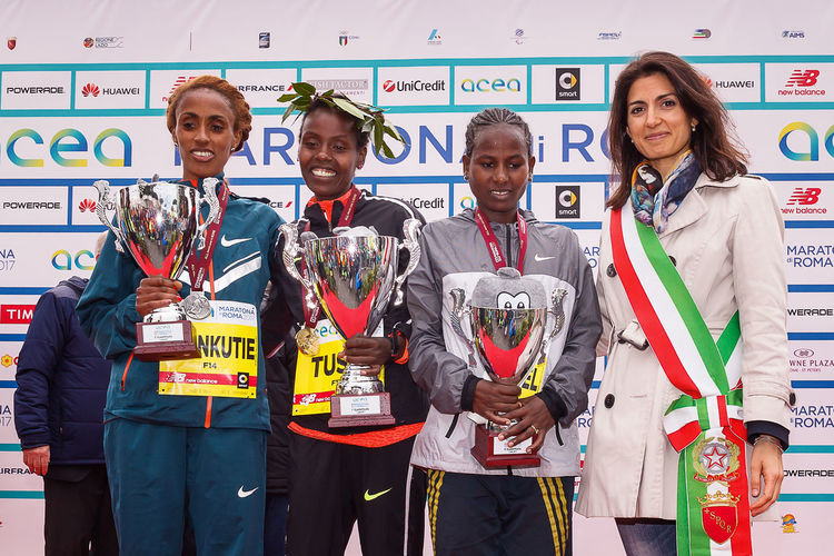 Rome, Italy - April 2, 2017: The mayor of Rome Virginia Raggi on stage with the top three women's race of the 23rd marathon in Rome. At the center of Chota Rahma Tusa, first. To his right, Shankutie Mestawot Tadesse, second place. To his left, Gebremeskel Ababa Tekulu, third place. Athletes Athletes; Award; Awards Color; Day Ethiopian; Kenyan; Marathon Medal Podium; Rome Marathon Rome Marathon 2017 Rome Marathon 23rd Runners; Winners