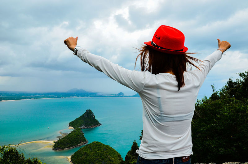 Rear view of woman with arms outstretched standing by sea against sky