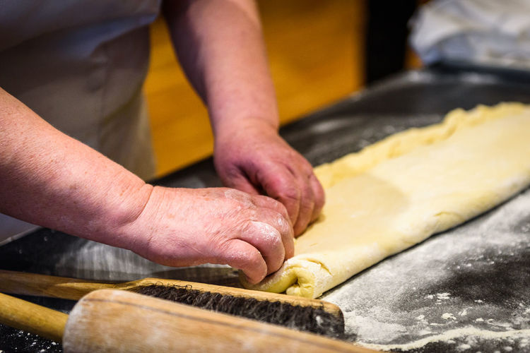 Midsection of man preparing cookies with dough at counter
