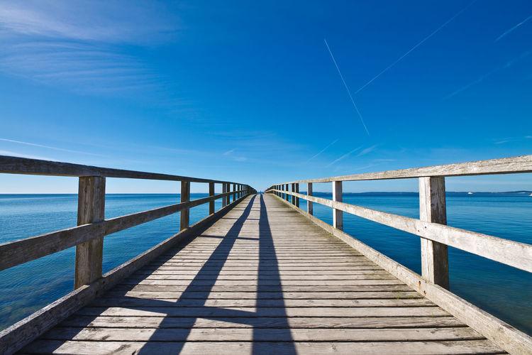 Pier Over Seascape Against Blue Sky