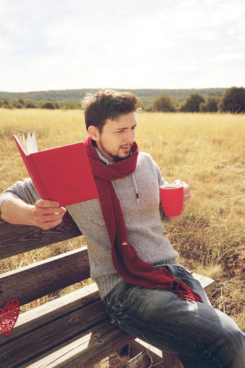 One Person Sitting Land Young Adult Leisure Activity Field Real People Relaxation Nature Casual Clothing Lifestyles Red Holding Young Men Day Landscape Three Quarter Length Sunlight Outdoors Reading Read Reading A Book Book