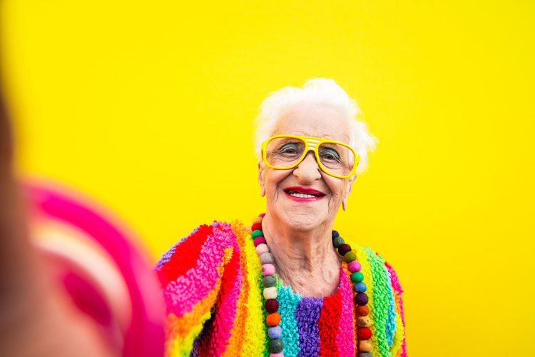 Portrait of smiling woman wearing colorful clothing against yellow background