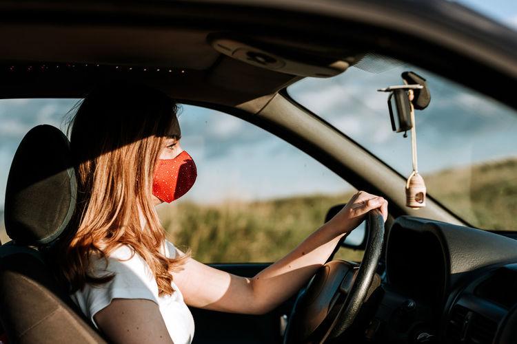 Side view of woman wearing flu mask sitting in car