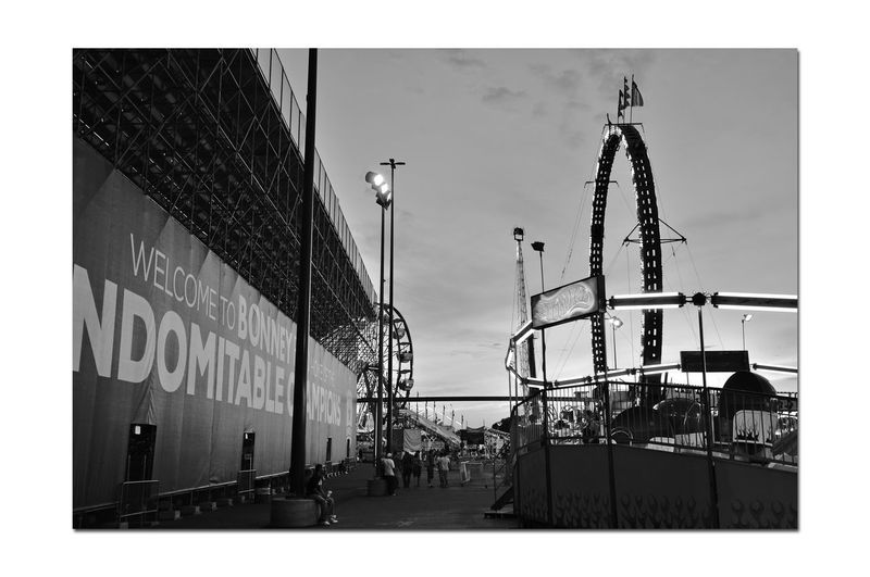 California State Fair 3 Sacramento, CA State Fair Exposition Grounds Grand Stand Ferris Wheel Park Rides Bnw_friday_eyeemchallenge Bnw_amusement_parks People Walking  Person Sitting Sundown Sunset Sunset Silhouettes Sunset_collection Neon Lights Flags Light Poles Monochrome_Photography Monochrome Black & White Black & White Photography Black And White Black And White Collection  Signs Text Sky Architecture Building Exterior Built Structure Amusement Park Ride