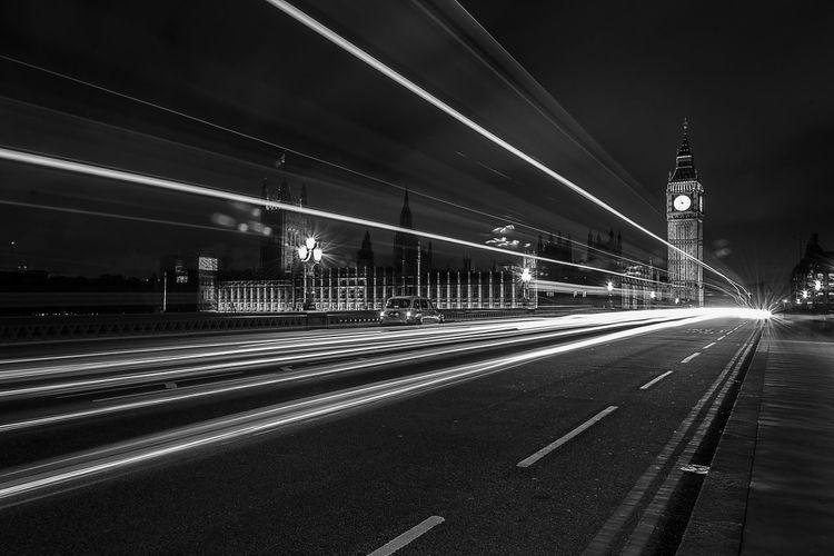 Light trails on westminster bridge against illuminated big ben at night