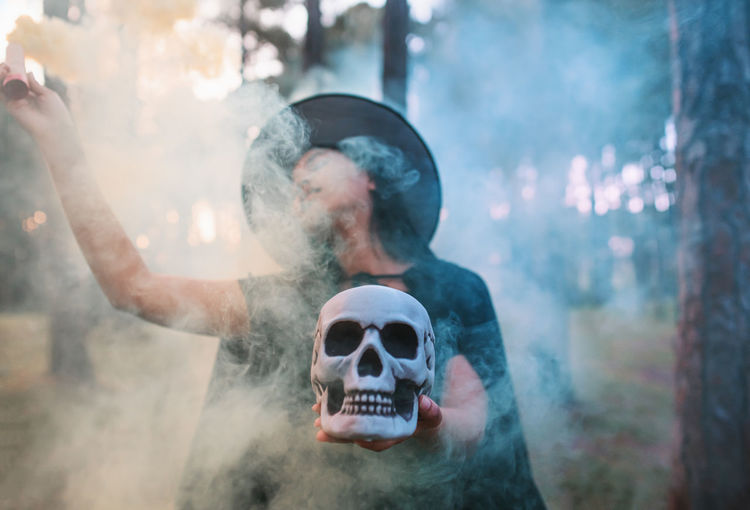Woman holding distress flare and skull while standing in forest