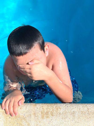 Shirtless boy swimming in pool
