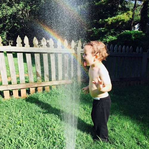 Side view of boy playing by sprinklers in garden