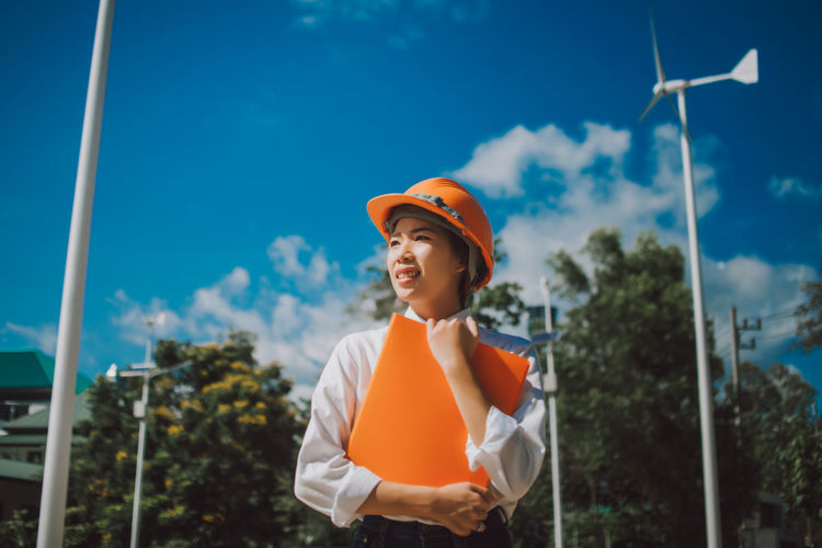 Low angle view of female engineer standing against windmill