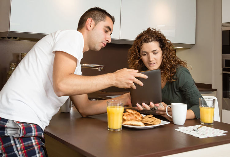 Happy young couple looking a digital tablet while having breakfast at home kitchen Family Fruit Girlfriend Thirties Relaxing Husband Boyfriend 30s Wife Relationship Adult Lifestyle Interior Love Cup Caucasian Healthy Two Coffee Glass Orange Girl Juice Meal Drink Together Young Woman Kitchen Man Indoors  Food Morning Technology Newspaper Digital Tablet News Smiling Cheerful Happiness Smile Happy Male Home People Female Couple Breakfast