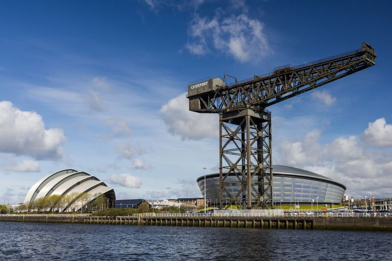 Scottish Exhibition And Conference Centre And Finnieston Crane By Clyde River Against Blue Sky