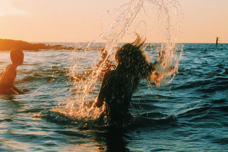 Outdoors Day Water Motion Sea Real People Splashing Lifestyles Sunset Leisure Activity Fun Wave Nature Beauty In Nature Enjoyment Standing Horizon Over Water