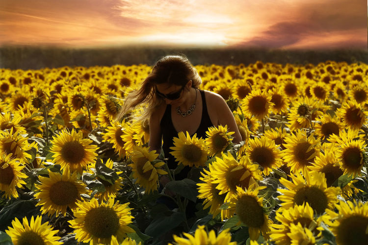 Beautiful Woman Standing On Sunflower Field During Sunset