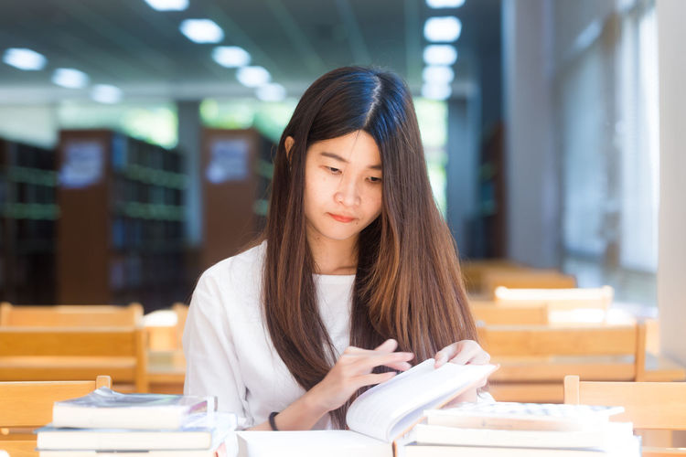 Portrait of young woman reading book on table