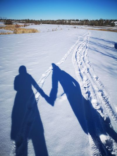 Shadow of people on snow covered field
