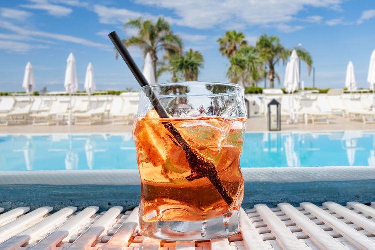 Close-up of drink on table by swimming pool against sky