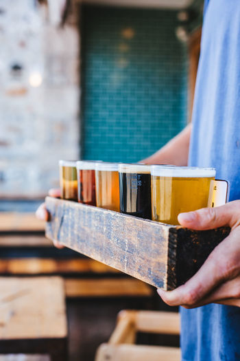 Midsection of man carrying various beer glasses in restaurant