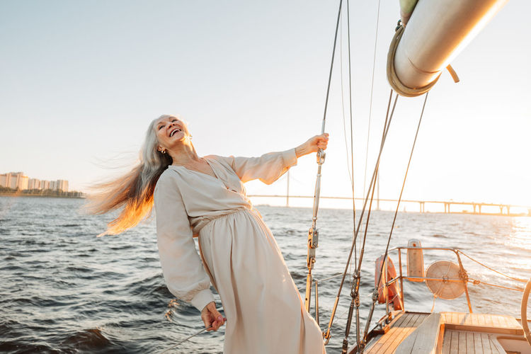 Smiling senior woman standing on boat at sea