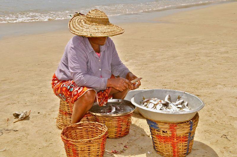 Senior woman selling fish at beach