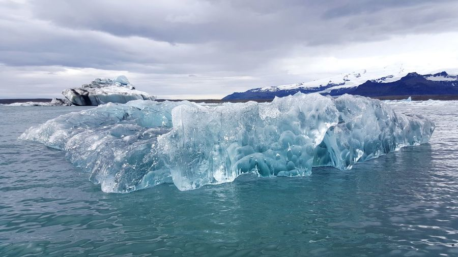 Ice Formation Floating On Sea Against Cloudy Sky