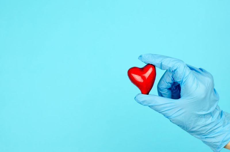Close-up of hand holding heart shape over blue background