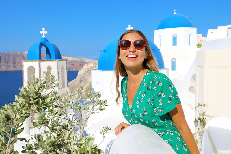 Architecture Beautiful Woman Belief Blue Dome Church Blue Domes Built Structure Casual Clothing Day Fashion Front View Leisure Activity Lifestyles Nature Oia One Person Outdoors Place Of Worship Real People Religion Santorini Santorini Church Smiling Spirituality Three Quarter Length Young Adult