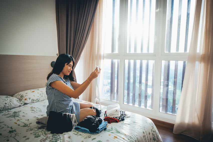 Curtain Window One Person Full Length Real People Sitting Furniture Indoors  Lifestyles Casual Clothing Bed Home Interior Leisure Activity Young Adult Young Women Black Hair Women Day Hairstyle Teenager