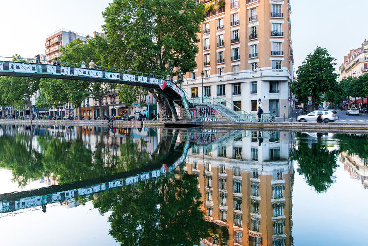 Reflection of bridge and trees on canal in city