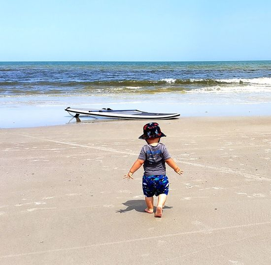 Rear view of baby boy walking at beach against sky