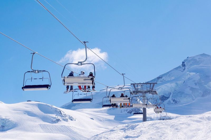 Overhead Cable Car Over Snowcapped Mountain Against Blue Sky