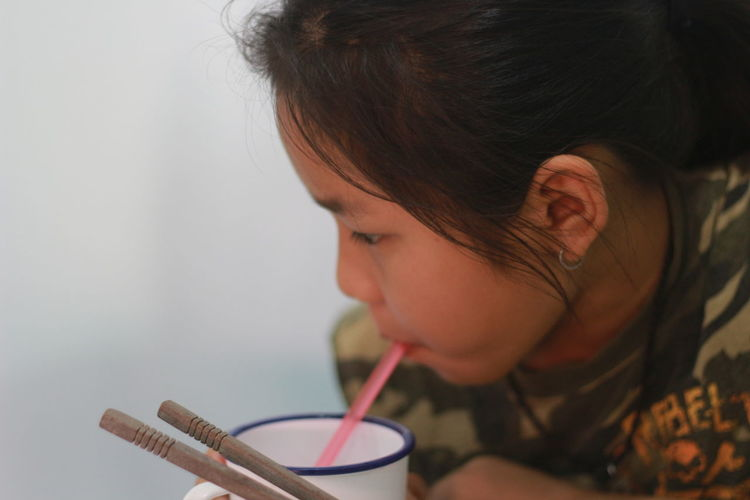 Close-up of girl drinking juice in cup
