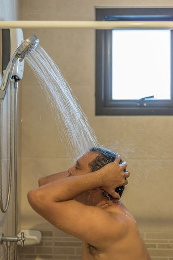 Shirtless Man Bathing In Bathroom